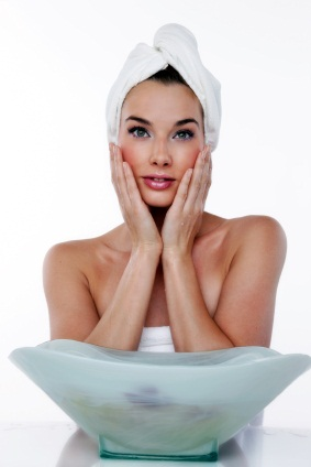 Woman wearing towel and hair in towel touching sides of face in front of spa water bowl
