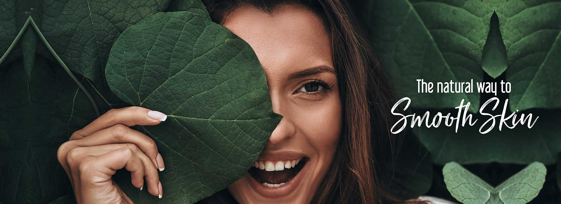 Woman smiling holding palm leaf over half of face next to The natural way to Smooth Skin text