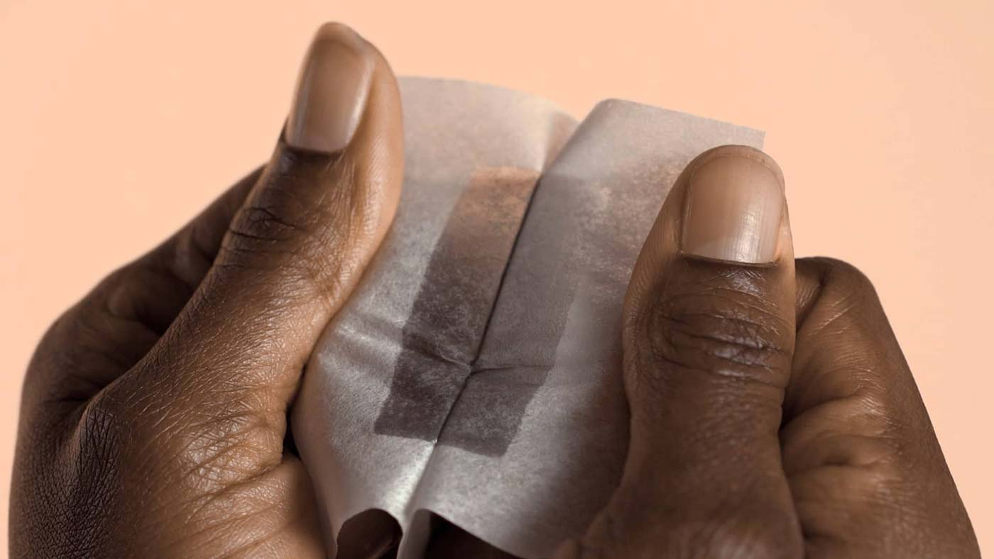 Close up of woman peeling apart Nad's Charcoal Body Wax Strips