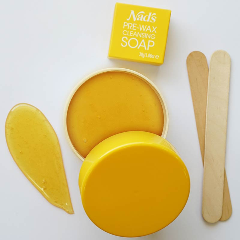 Nad's Natural Sugar Wax open container, smear of wax, pre-wax cleansing soap, and wooden applicators