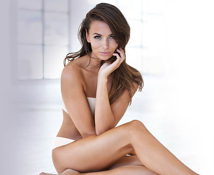 Woman in white swimsuit sitting on with hand on side of face